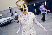 27 MAY 2011 - PHOENIX, AZ: A zombie walks through the Phoenix Comicon trade show Friday. Phoenix Comicon opened Thursday and featured a Zombie Walk through downtown Phoenix Friday night. Hundreds of people participated in the Zombie Walk, both as Zombies and as Zombie hunters. This year's Comicon includes appearances by Leonard Nimoy (Star Trek), Adam Baldwin (Firefly and Chuck), Stan Lee (Marvel Comics), Nicholas Brendon (Buffy the Vampire Slayer) and others. Activities include costuming workshops, role playing games and a Geek Prom.     Photo by Jack Kurtz