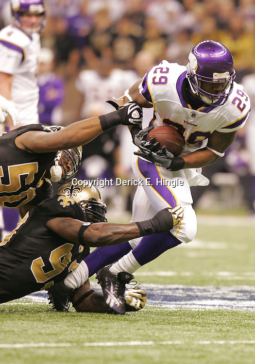 Jan 24, 2010; New Orleans, LA, USA; Minnesota Vikings running back Chester Taylor (29) escapes the grasp of New Orleans Saints linebacker Marvin Mitchell (50) and defensive end Bobby McCray (93) during a 31-28 overtime victory by the New Orleans Saints over the Minnesota Vikings in the 2010 NFC Championship game at the Louisiana Superdome. Mandatory Credit: Derick E. Hingle-US PRESSWIRE