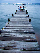 A group of friends dines at the end of a dock in the West End of Roatan, Honduras.