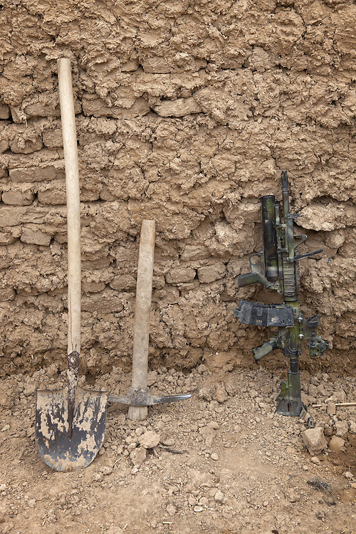 A farmers tools lean against a wall next to a Diemaco C7 assault rifle as British soldiers of 16 Air Assault Bde's elite BRF (Brigade Reconnaissance Force) move from compound to compound searching for weapons and explosives as part of an operation in the Western Dasht, Helmand Province, Southern Afghanistan on the 18th of March 2011.