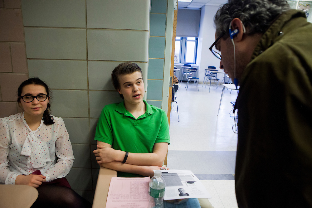 NEW YORK, NY - MARCH 27, 2015: Studennts Nadia Filanovsky and Winston Venderbush serve as some of the gatekeepers who tells parents when it's their turn to speak with a teacher during parent-teacher conferences at Stuyvesant High School. Each parent unit is allotted three minute with each teacher.