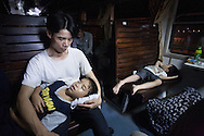 A boy sleeps on his father's lap while traveling by train from Hanoi to Saigon, Vietnam, Southeast Asia