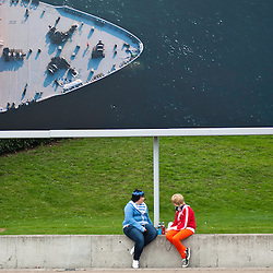London, UK - 26 October 2012: two visitors sit under a large commercial banner outside the Excel during the Comic Con 2012 - MCM Expo - where book fans, videogame lovers, anime devotees, cosplay wearers gather every year