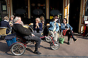 Een man op een ligfiets schuift even aan bij het terras bij Springhaver.<br /> <br /> A man on a recumbent bike is talking at a terrace in Utrecht.