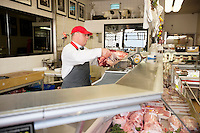 Butcher weighing beefsteak on scale in store