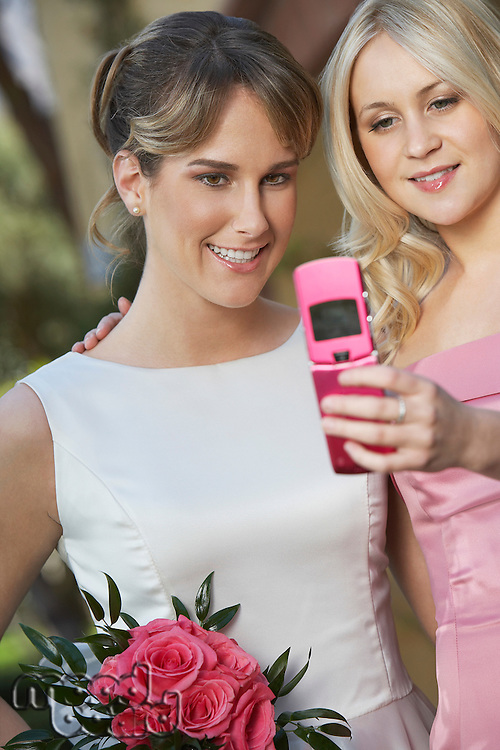 Bridesmaid photographing bride and self with mobile phone