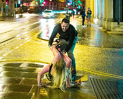 "© Licensed to London News Pictures . 22/12/2018 . Manchester , UK . A man helps a woman who has slipped over on the pavement on Cross Street . Revellers out in Manchester City Centre overnight during "" Mad Friday "" , named for historically being one of the busiest nights of the year for the emergency services in the UK . Photo credit : Joel Goodman/LNP"