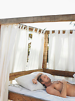 Man lying on four poster bed on beach half length
