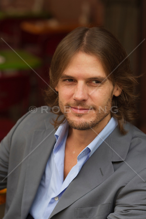 man with long hair in a suit with no tie out on the street in New York City