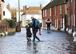 A family struggle through a flooded street in the village of Bridge, Kent , United Kingdom. Sunday, 9th February 2014. Picture by Stephen Lock / i-Images