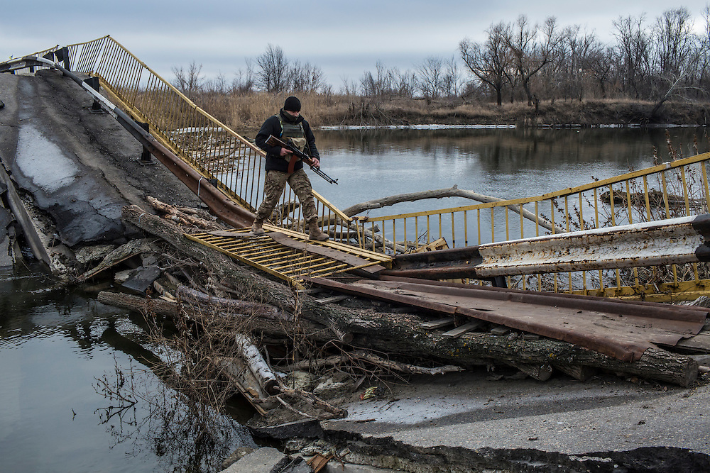 A Ukrainian soldier guards a destroyed bridge over the Siverskyi Donets River, which separates Ukrainian territory from that controlled by pro-Russian rebels, on Wednesday, February 10, 2016 in Trokhizbenka, Ukraine.