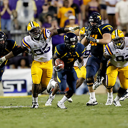Sep 25, 2010; Baton Rouge, LA, USA; West Virginia Mountaineers running back Noel Devine (7) runs away from LSU Tigers defensive tackle Drake Nevis (92) and defensive tackle Lazarius Levingston (95) during the second half at Tiger Stadium. LSU defeated West Virginia 20-14.  Mandatory Credit: Derick E. Hingle