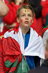 LILLE, FRANCE - Friday, July 1, 2016: A young Wales supporter wrapped in a flag with a painted face in the stands ahead of the UEFA Euro 2016 Championship Quarter-Final match against Belgium at the Stade Pierre Mauroy. (Pic by Paul Greenwood/Propaganda)