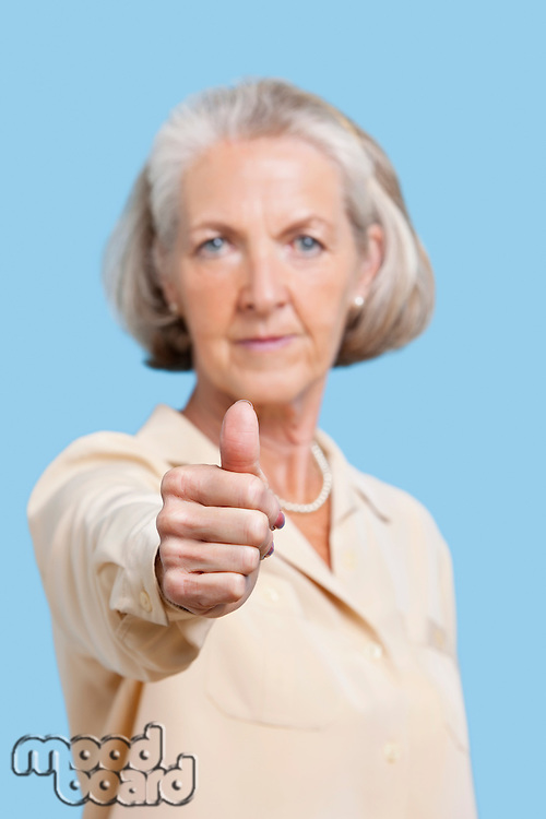 Portrait of senior woman in casuals gesturing thumbs up against blue background