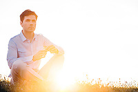 Thoughtful man looking away while sitting on grass against clear sky