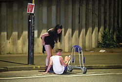 © Licensed to London News Pictures . 26/08/2016 . Manchester , UK . A woman lifts her friend off the road after he fell from an airport baggage trolley that she had used to push him across the road . Revellers in Manchcester's Gay Village for 2016 Manchester Gay Pride Big Weekend . Photo credit : Joel Goodman/LNP