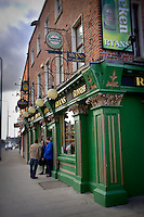 Ryan's Pub, a traditional Irish pub in Dublin, Ireland with people hanging out around the entrance