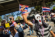 "14 JANUARY 2014 - BANGKOK, THAILAND: An anti-government protestor wearing a mask from the movie ""Scream"" in front of Royal Thai police headquarters. Hundreds of protestors picketed police headquarters because they accuse the police of siding with the government during the protests. Tens of thousands of Thai anti-government protestors continued to block the streets of Bangkok Tuesday to shut down the Thai capitol. The protest, ""Shutdown Bangkok,"" is expected to last at least a week. Shutdown Bangkok is organized by People's Democratic Reform Committee (PRDC). It's a continuation of protests that started in early November. There have been shootings almost every night at different protests sites around Bangkok, but so far Shutdown Bangkok has been peaceful. The malls in Bangkok are still open but many other businesses are closed and mass transit is swamped with both protestors and people who had to use mass transit because the roads were blocked.     PHOTO BY JACK KURTZ"