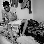 Au port d'Imi Ouaddar, petit village de pêcheurs niché dans la commune rurale de Tamri, à 30 kilomètres d'Agadir, les mailles se tendent et se tissent avec patience et minutie. Un savoir-faire artisanal qui se perd, souvent transmis de père en fils. « J'ai été initié aux techniques de ramendage, la réparation de filets, à l'âge de 10 ans et je suis payé 1500 DH par mois ». A 25 ans, Fadah, fils de pêcheur, a des années de métier derrière lui et autant de désillusions. Chaque jour, c'est plus de 50 mètres de mailles qui passent sous l'aiguille du jeune marin. Appartenant aux armateurs de bateaux, les filets qu'ils réparent coûtent entre 20000 et 30000 dirhams.