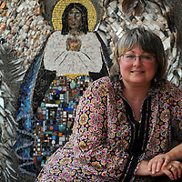 Artist  Tricia Huffman poses in front of a large mosaic angel which took her a year to create, while in her downtown studio on Thursday. Melanie Maxwell | AnnArbor.com