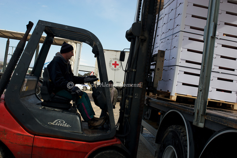 ISRAEL, GOLAN : Apples (white boxes) loading operations in  Kuneitra crossing Sirian-Israeli check point on Alpha line,  on February 15, 2010. ©ICRC/ ALESSIO ROMENZI