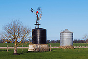 Windmill, water tank and grain silo in farm paddock in rural country Victoria, Australia.