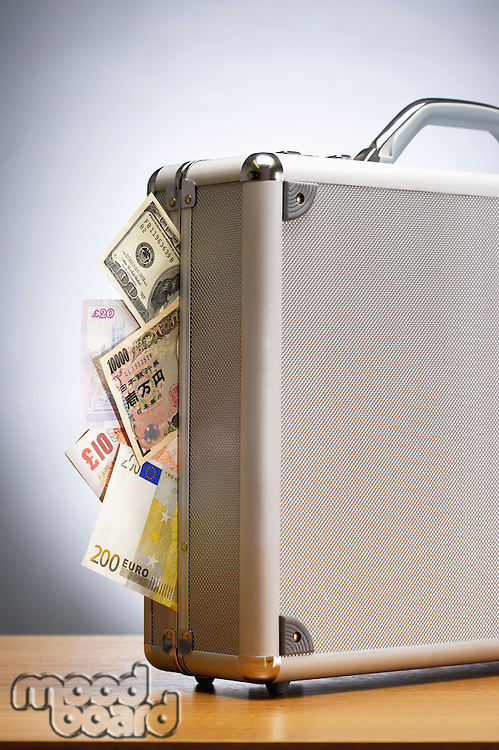 Metal briefcase full of cash on table