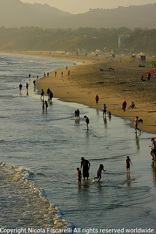 A view of people enjoying the late afternoon sun on the beach of Santa Monica California.