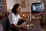 Shashi Kanth, a call center worker, eats a late lunch while watching MTV at his home before going to work in Bangalore, India. (Shashi Kanth is featured in the book What I Eat: Around the World in 80 Diets.) Shashi loves his mother's traditional southern Indian food at home, but when he's at work his dinner options are KFC and Beijing Bites, the fast-food restaurants on the ground floor of the high-rise where he works, located on the edge of Bangalore. Like many of his co-workers, Shashi relies on quick fast food meals, candy bars, and coffee, to sustain him through the long nights spent talking to westerners about various technical and billing problems. MODEL RELEASED.