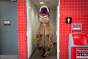 UNITED KINGDOM, London: 27 October 2017 A cosplay fan dressed as an inflatable Tyrannosaurus Rex leaves a public bathroom during the MCM London Comic Con. The convention, which runs all this weekend at the Excel Centre, will see thousands of cosplay and comic book fans visit the venue. Rick Findler / Story Picture Agency
