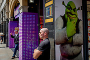 The fantasy monster Shrek and a bald man adopting the same postural echo outside a tourist trinket shop near Piccadilly Circus, on 9th May 2018, in London, England. Shrek is a 2001 American computer animated adventure fantasy comedy film loosely based on William Steig's 1990 fairy tale picture book