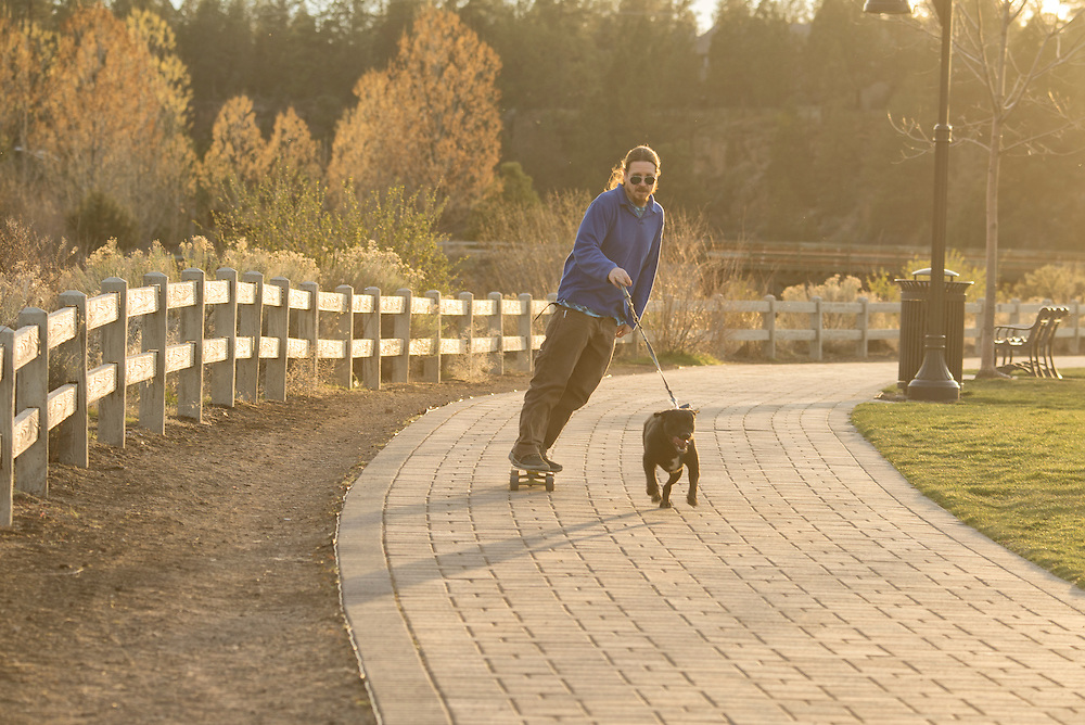USA, Oregon, Central Oregon, Bend, man with dog on skates
