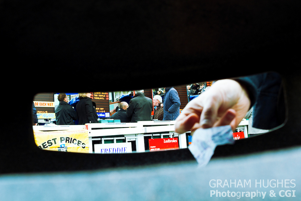 Male hand placing losing betting slip into bin. Focus on bookmakers behind.