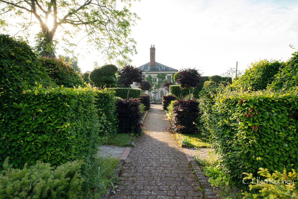 The view along a brick path surrounded by topiary to the house at the Laskett Gardens, Much Birch, Herefordshire, UK