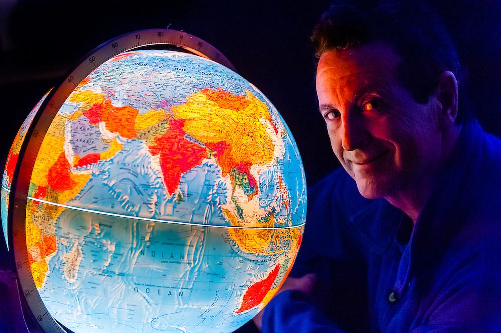 Blaine Harrington III looking at world globe, Littleton, Colorado USA