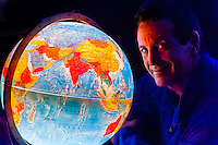 Blaine Harrington III looking at world globe, Littleton, Colorado USA