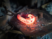 25 JANUARY 2016 - BANGKOK, THAILAND: Chain links straight out of the furnace are still glowing red in a small one person workshop that makes heavy chains for boat anchors. The metal for the chains is heated until it glows red and then it's pounded into shape. The Talat Noi neighborhood in Bangkok started as a blacksmith's quarter. As cars and buses replaced horse and buggy, the blacksmiths became mechanics and now the area is lined with car mechanics' and blacksmiths' shops.          PHOTO BY JACK KURTZ