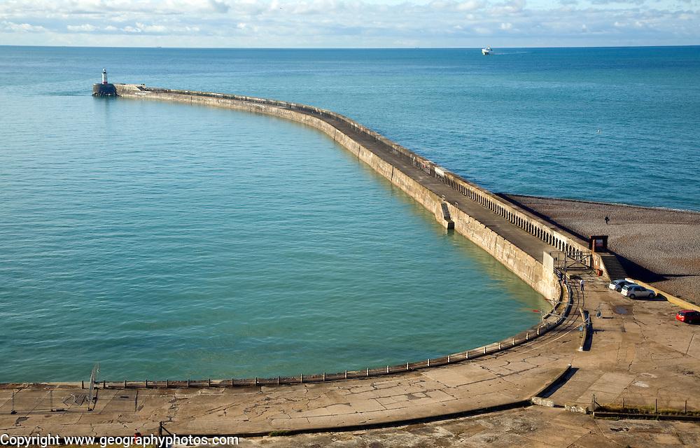 Large breakwater concrete groyne Newhaven, East Sussex, England. Sediment accumulation illustrates longshore drift.