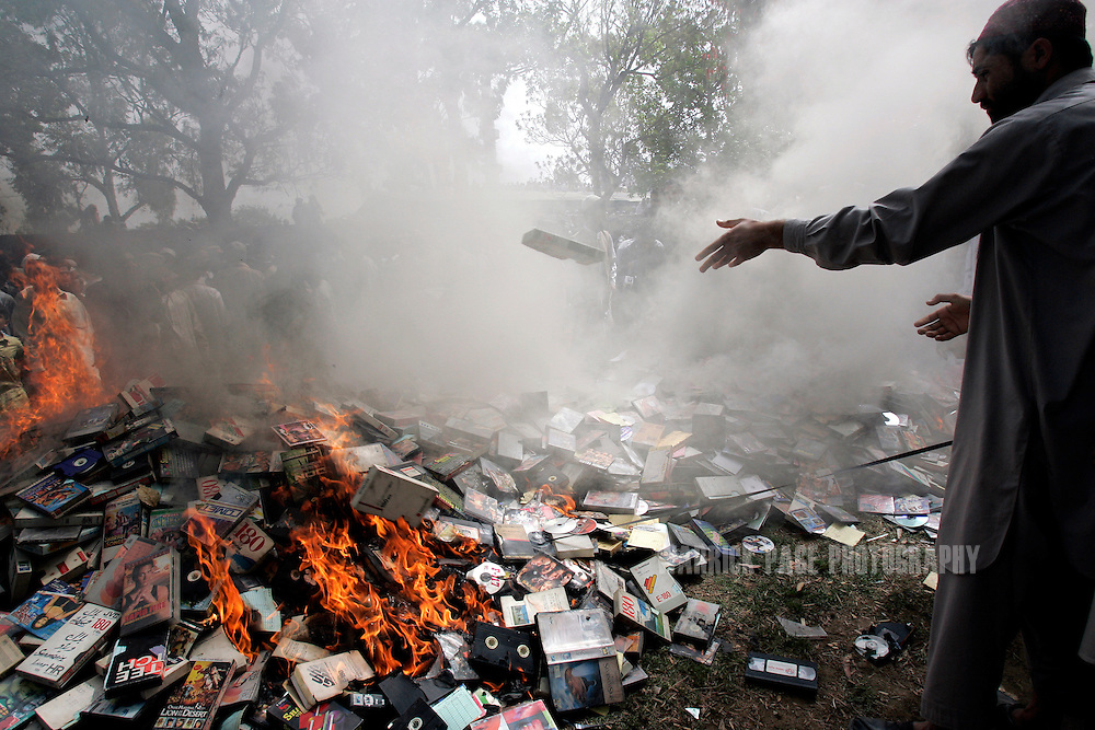 "A religious student of the radical Islamist Red Mosque throws CDs and DVDs onto a burning pile in an ""anti-vice"" drive after Friday prayers in Islamabad, Pakistan, Friday, April 6, 2007. (Photo by Warrick Page)"
