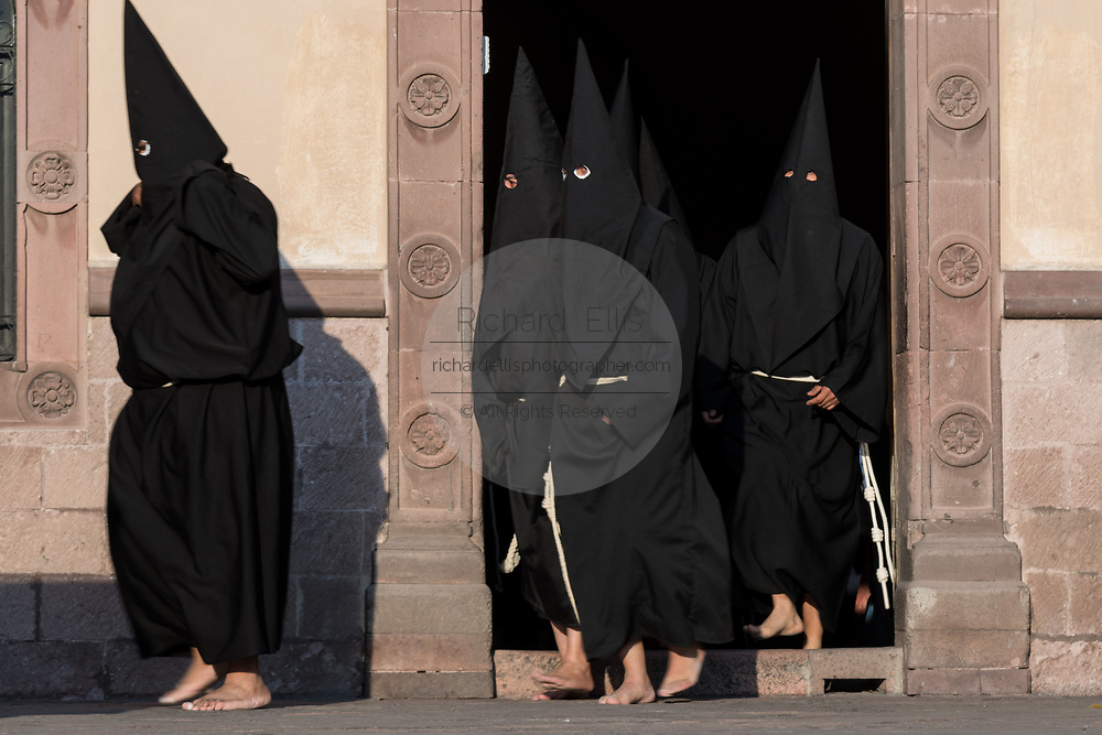 Hooded penitents walk out from the Church of the Holy Cross at the start of the Procession of Silence as part of Holy Week March 30, 2018 in Querétaro, Mexico. The penitents, known as Nazarenes, carry heavy crosses and drag chains in a four hour march to recreate the pain and suffering during the passion of Christ.