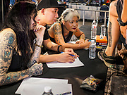 28 OCTOBER 2018 - BANGKOK, THAILAND: Judges score a man's tattooed leg during judging of the Realistic division at the 2018 MBK Center Tattoo Fest. Tatoo artists from around the world came to participate in the festival, which featured both modern (using tattoo machines) and traditional methods (done by hand with long needles) of tattooing.    PHOTO BY JACK KURTZ