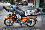 A man is sleeping on his motorbike in a street of Phnom Penh, Cambodia. Khmer people can be very creative in the way they rest. <br /> Photo by Lorenz Berna