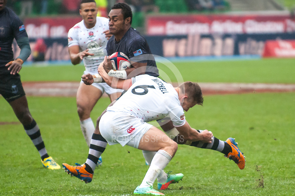 Fiji's Donasio Ratubuli is tackled by England's Tom Mitchell. Action from the IRB Emirates Airline Glasgow 7s at Scotstoun in Glasgow. 4 May 2014. (c) Paul J Roberts / Sportpix.org.uk