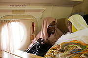 Dr Safaa Elagib Adam and Maha Faraigon are seated near the window on a flight to attend the first-ever international Conference on Womens' Challenge in Darfur. Discussing conference matters, they sit in a chartered Russian Antonov aircraft during flight to Al Fasher (also spelled, Al-Fashir) in north Darfur where women from remote parts of Sudan gathered to discuss peace and political issues. The short flight saves them a hazardous five-day drive by road, known for extreme acts of violence by rebels and Janjaweed soldiers.