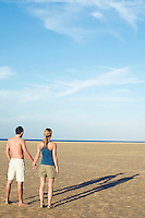 Couple standing on beach looking out to sea back view