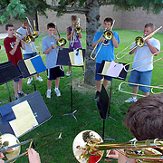 "The trombone section of the MOC-Floyd Valley band seek relief from the August heat by practicing  under the shade of a pine tree during band camp in Orange City during the  summer.  ""There are bands all over the state rehearsing right now with one goal in mind - defeat the Pride of the Dutchmen Marching Band in competition this year,"" said band director Steve Connell."