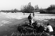 Utrecht Netherlands 22 January 2017. A group of young guys changing shoes after having been ice skating on an natural pond near Utrecht.