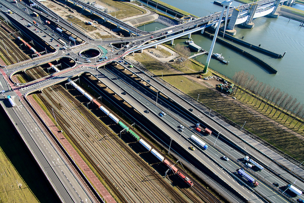 Nederland, Zuid-Holland, Rotterdam, 18-02-2015. A15 ter hoogte van het Hartelkruis. Goederentrein op Betuweroute richting Maasvlakte II.<br /> Motorway A15 and freight railway, connecting Port of Rotterdam with hinterland.<br /> luchtfoto (toeslag op standard tarieven);<br /> aerial photo (additional fee required);<br /> copyright foto/photo Siebe Swart