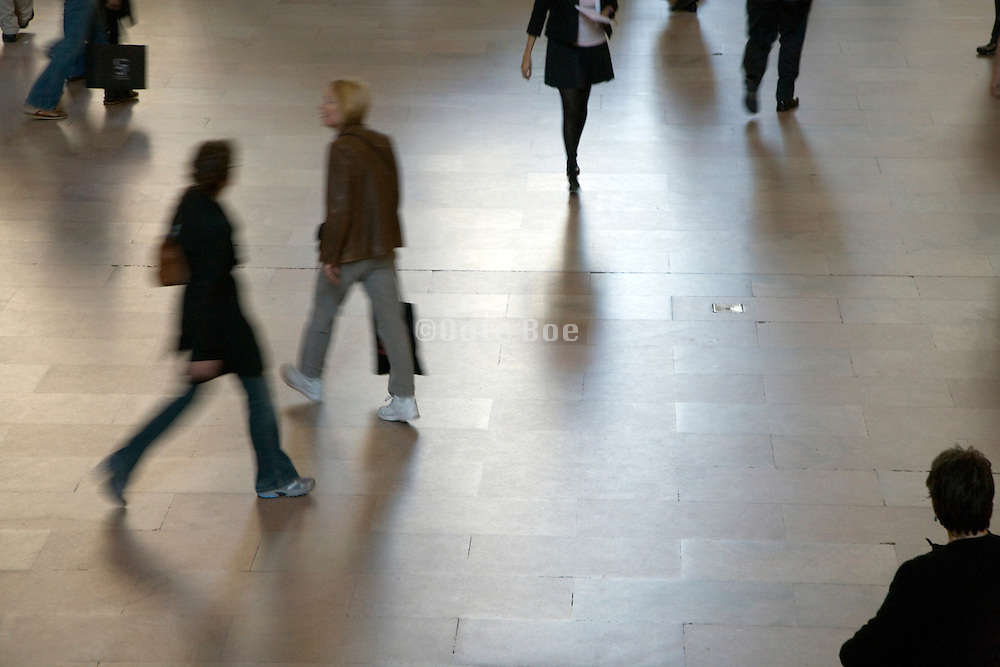 silhouette of a people walking in a large lobby terminal