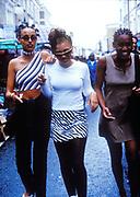 Three girls walking down a market road, London UK 1990's